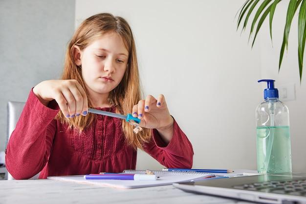 Educación a distancia en línea. colegiala estudiando en casa con una computadora portátil y haciendo la tarea escolar. afilar un lápiz con un sacapuntas, enfoque selectivo