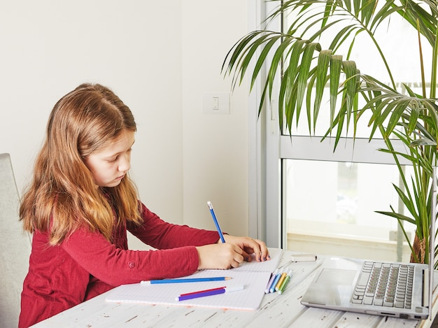 Educación a distancia en línea. colegiala estudiando en casa con una computadora portátil y haciendo la tarea escolar. cuadernos de entrenamiento y rotuladores de colores sobre la mesa