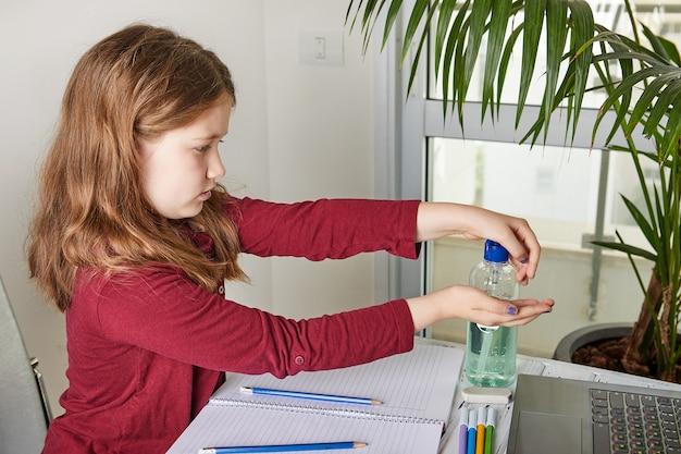 Educación a distancia en línea. colegiala estudiando en casa con una computadora portátil y haciendo la tarea escolar. se frota las manos contra el coronavirus con gel con alcohol 70 por ciento