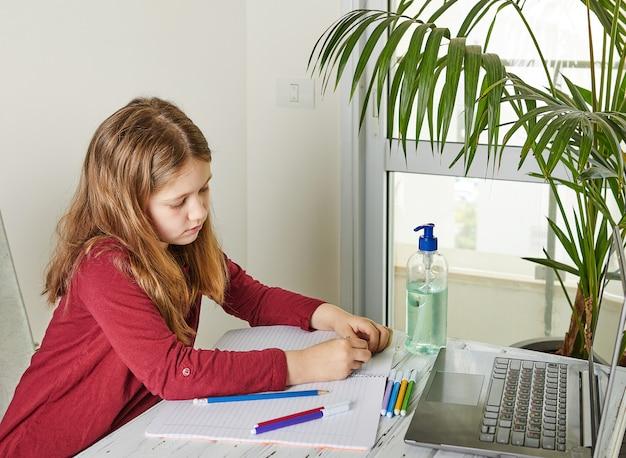 Educación a distancia en línea. colegiala estudiando en casa con una computadora portátil y haciendo la tarea escolar. libros de capacitación y rotuladores de colores sobre la mesa, gel con alcohol 70 por ciento