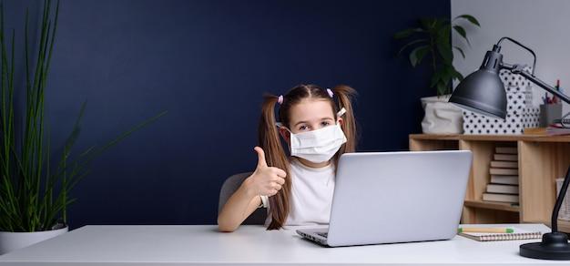 Educación a distancia en línea. colegiala en máscara médica estudiando en casa, trabajando en la computadora portátil y haciendo la tarea escolar. cuarentena de coronavirus.