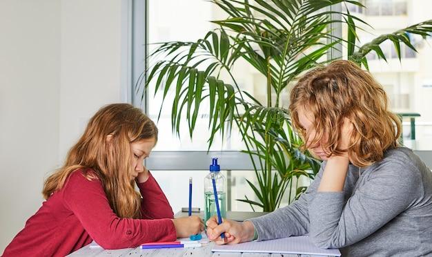 Educación a distancia en línea. las colegialas hermanas mayores y menores estudian en casa con una computadora portátil y hacen la tarea escolar.