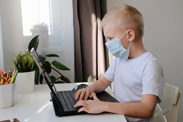 Educación a distancia en línea. lindo niño caucásico haciendo la tarea con el portátil en casa mientras está en cuarentena del virus corona de la epidemia