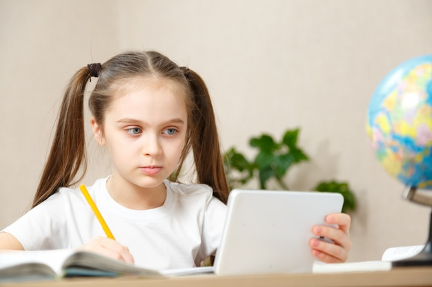 Educación a distancia en línea la niña de la escuela hace la tarea en la tableta en casa. cuarentena