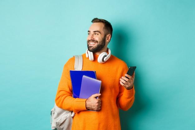 Educación. estudiante varón guapo con auriculares y mochila, usando teléfono móvil y sosteniendo cuadernos, sonriendo feliz, de pie sobre fondo turquesa.