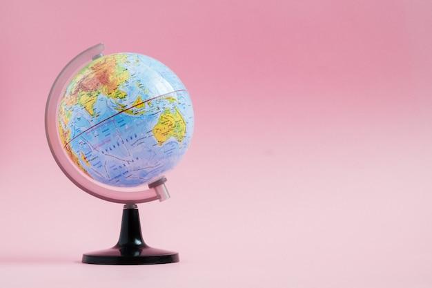 Educación de historias de aventuras con globo terráqueo sobre fondo rosa