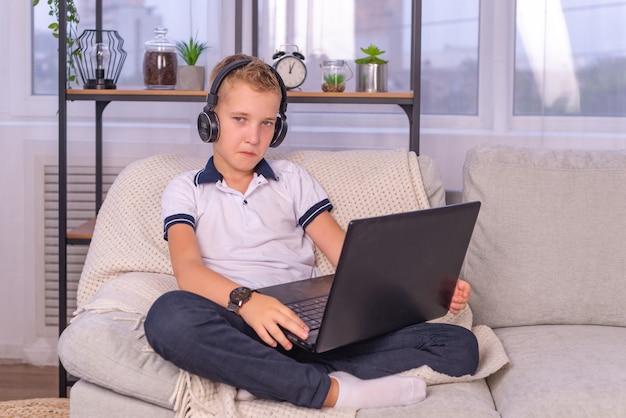 Educación en línea de aprendizaje a distancia un niño escolar estudia en casa y hace la tarea escolar a hom