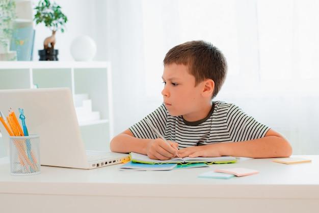 Educación en línea a distancia. un niño en edad escolar estudia en casa y hace los deberes escolares. un aprendizaje a distancia desde casa.