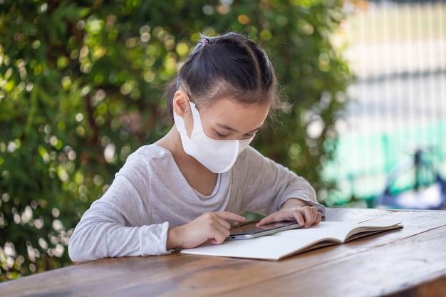 Educación en línea a distancia. niño con máscara para ver una lección en línea.
