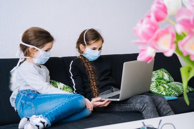 Educación en línea, educación a distancia, educación en el hogar. niños que estudian la tarea durante la lección en línea en casa en la tableta de la computadora portátil y que sostienen la videollamada. distancia social en cuarentena. autoaislamiento