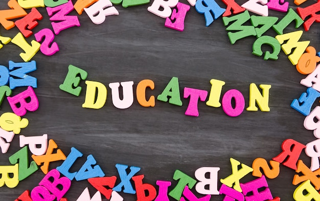 Educación de la palabra hecha de letras de colores sobre un fondo de madera negra