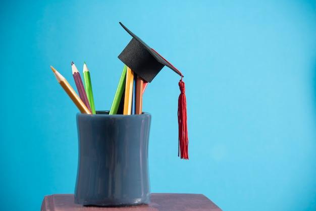 Educación y vuelta al concepto de la escuela con tapa de graduación en lápices de colores en una caja de lápices