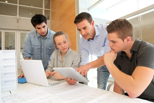 Educador con alumnos de arquitectura trabajando en tableta electrónica.
