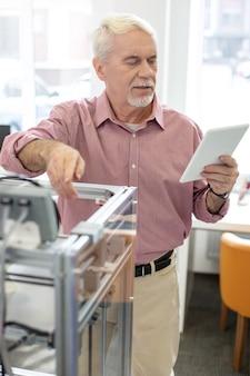 Educándose a sí mismo. hombre mayor alegre leyendo un manual en tableta y aprendiendo a operar una impresora 3d