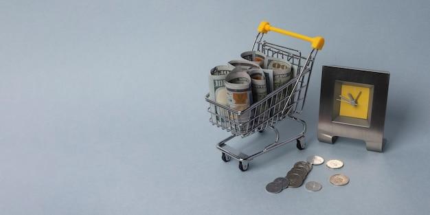 Efectivo en carrito de compras con relojes. hora de comprar, a la venta. banner con espacio de copia