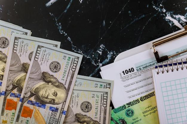 Efectivo en dólares estadounidenses, contabilidad financiera y cuaderno en blanco 1040 formulario de impuestos individuales temporada de impuestos