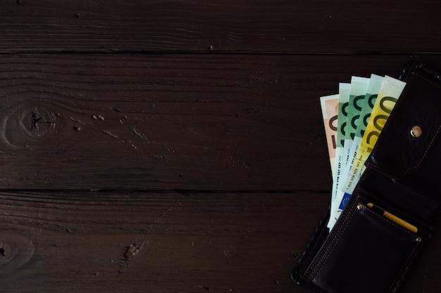 Efectivo en euros en la billetera marrón sobre fondo de madera