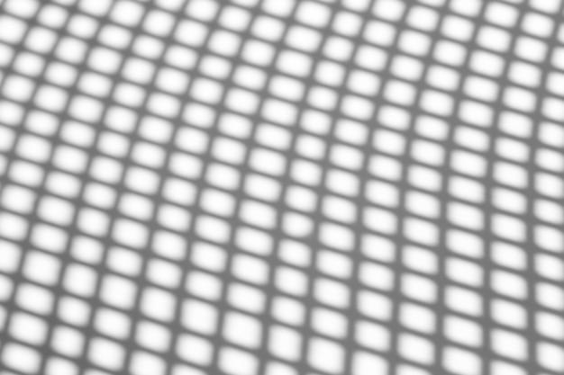 Efecto de superposición de sombras. sombras de líneas de cuadrícula o rejilla de una cerca o barandilla en una pared blanca limpia en un día despejado y soleado.