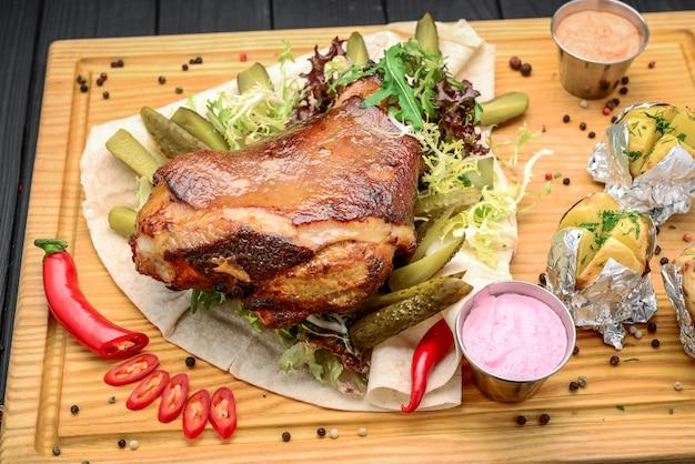 Eisbein al horno con wegetables en tablero de madera.