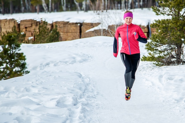 Ejecutan mujer deporte. corredor femenino trotar en el bosque de invierno frío vistiendo ropa deportiva cálida.