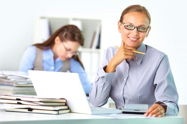 Ejecutiva con gafas en su lugar de trabajo