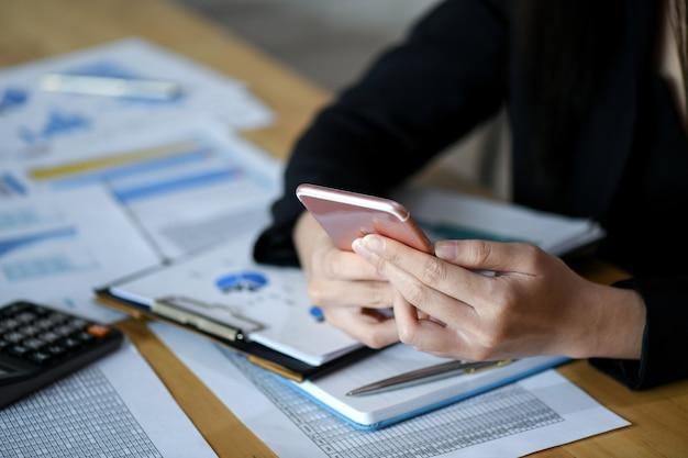 Ejecutivas están utilizando teléfono inteligente en la oficina.