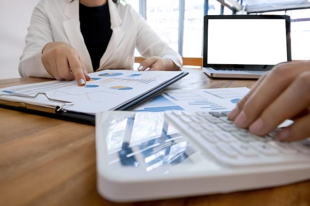 Ejecutivo análisis en papel de datos y contador utilizando calculadora en la oficina con pantalla en blanco portátil, concepto de negocio