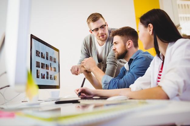 Ejecutivo asistiendo a colegas en la oficina creativa
