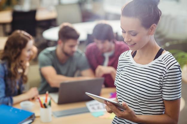 Ejecutivo de operaciones de sexo femenino que usa la tableta digital