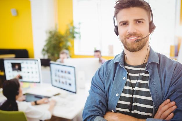 Ejecutivo feliz con auriculares en la oficina creativa