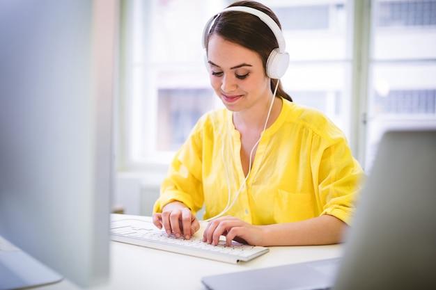 Ejecutivo feliz escribiendo en el teclado en la oficina creativa