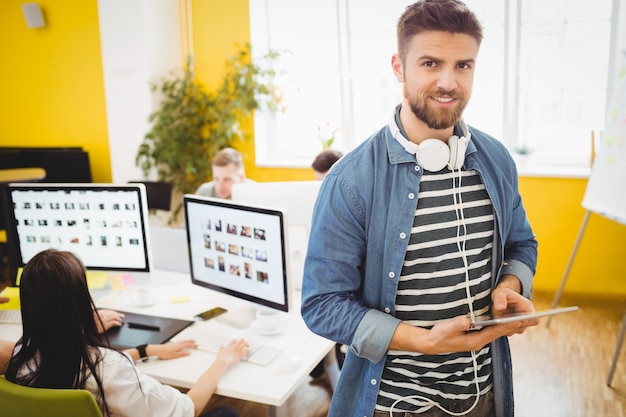 Ejecutivo feliz usando tableta digital en la oficina creativa