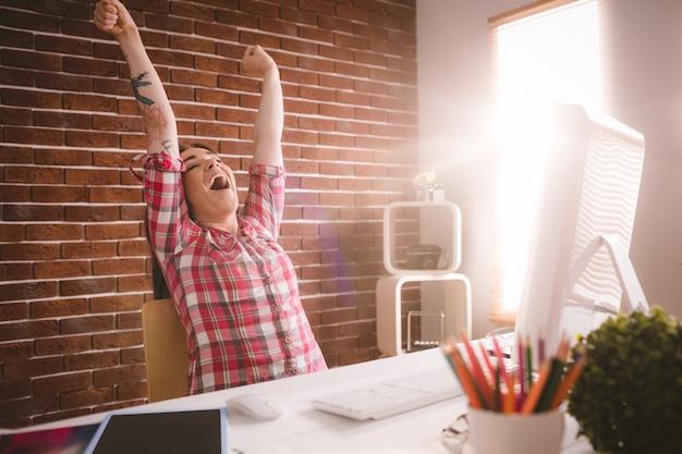 Ejecutivo femenino estirando las manos en su escritorio