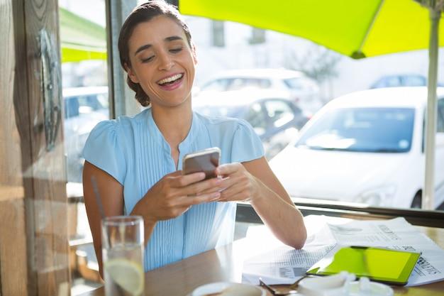 Ejecutivo femenino a través de teléfono móvil en el café