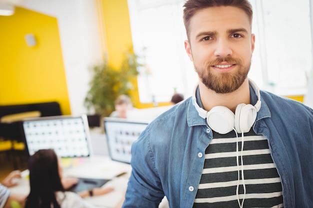 Ejecutivo guapo con auriculares en la oficina creativa