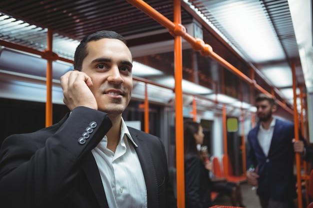 Ejecutivo hablando por teléfono móvil en tren