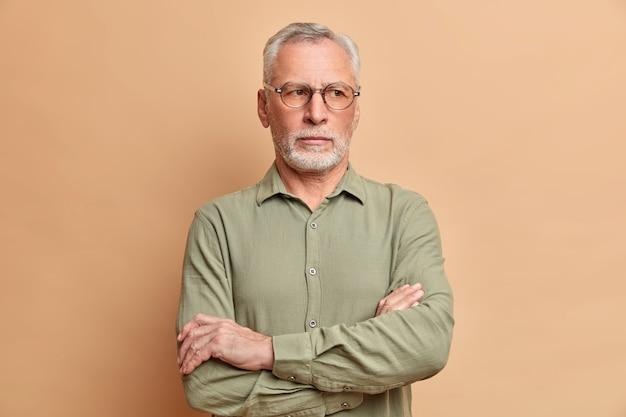 El ejecutivo maduro del hombre barbudo mantiene los brazos cruzados y se para en el interior pensativo piensa en los planes futuros vestido con ropa formal aislada sobre la pared beige necesita pensar en algo