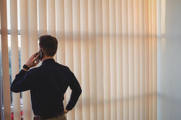 Ejecutivo masculino hablando por teléfono móvil cerca de las persianas