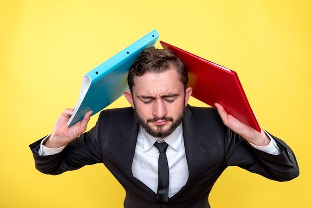 Ejecutivo masculino que se siente agotado debido a la confusión excesiva entre dos documentos