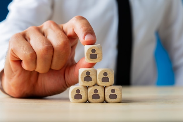 Ejecutivo de negocios apilando dados de madera con iconos de personas en forma de pirámide