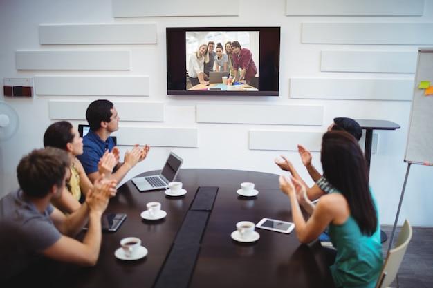 Ejecutivo de negocios aplaudiendo durante una videoconferencia