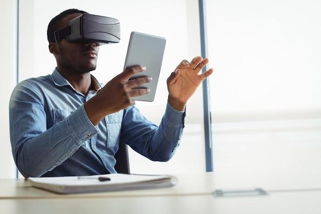 Ejecutivo de negocios con casco de realidad virtual y tableta digital