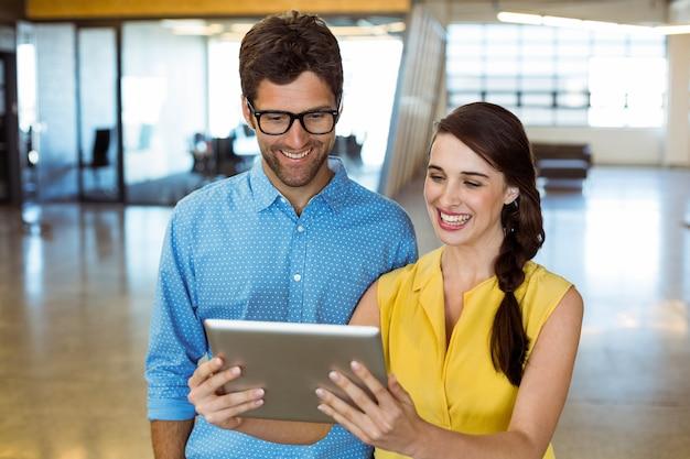 Ejecutivo de negocios y compañero de trabajo mirando tableta digital