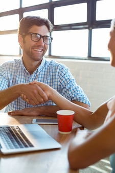 Ejecutivo de negocios dándose la mano con un compañero de trabajo