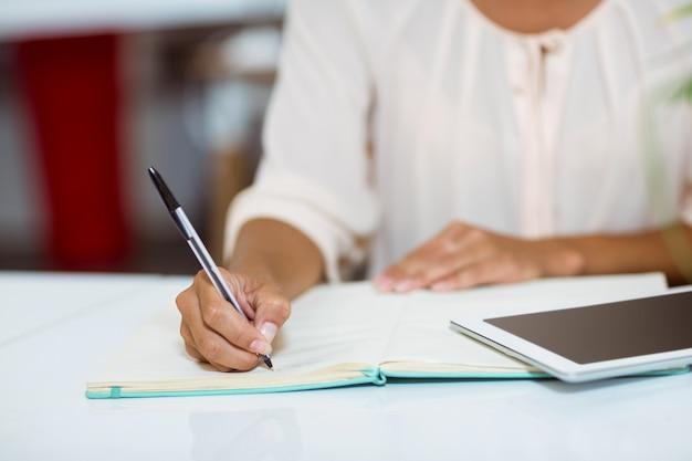 Ejecutivo de negocios escribiendo en diario