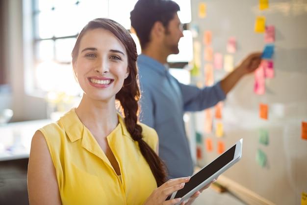 Ejecutivo de negocios femenino que sostiene la tableta digital