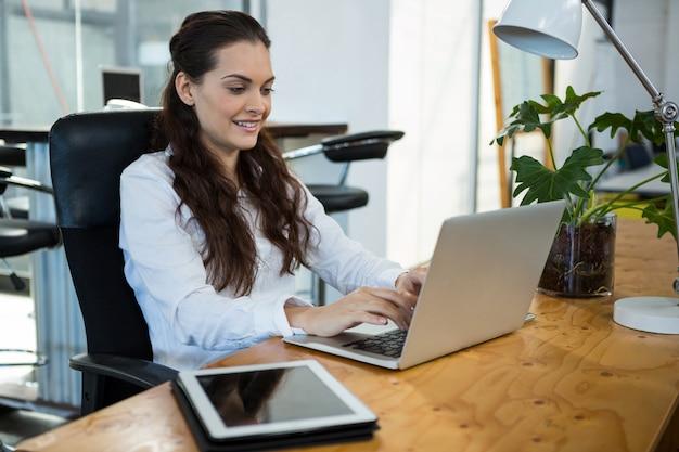 Ejecutivo de negocios femenino usando laptop