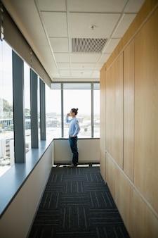 Ejecutivo de negocios hablando por teléfono móvil en el pasillo