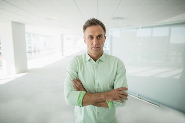 Ejecutivo de negocios de pie con los brazos cruzados en el pasillo de la oficina