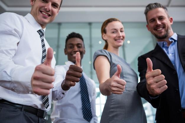 Ejecutivo de negocios que muestra los pulgares para arriba en la oficina